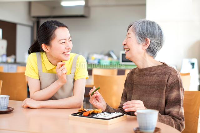 お弁当を食べるおばあちゃんと付きそう介護士の女性の写真素材 [FYI01345233]