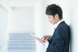タブレットを操作するビジネスマンの写真素材 [FYI01345464]