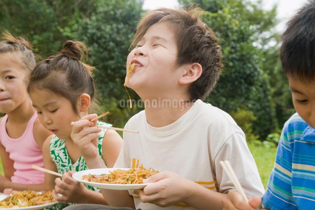 焼きそばを食べる子ども達の写真素材 [FYI01345505]