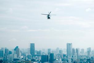 ビル群に向かって飛ぶヘリコプターの写真素材 [FYI01345547]