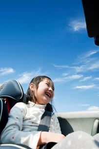 オープンカーに乗って笑う女の子の写真素材 [FYI01345565]