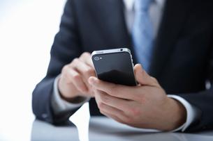 スマートフォンを操作しているビジネスマンの手の写真素材 [FYI01345665]