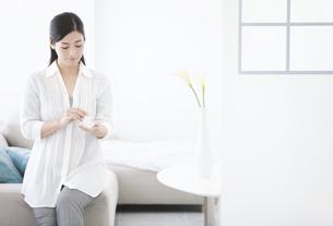 香水をつける女性の写真素材 [FYI01346515]
