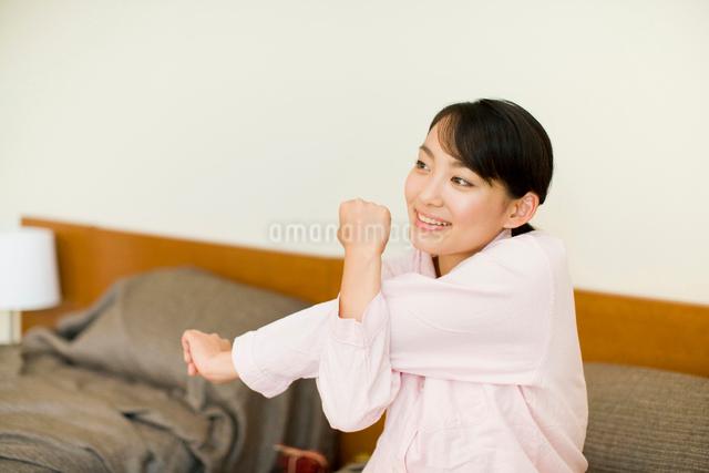ベッドでストレッチをする女性の写真素材 [FYI01346549]