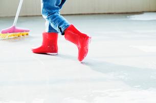 掃除をする子供の赤い長靴の写真素材 [FYI01347063]