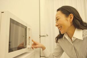 電子レンジのスイッチを押す女性の写真素材 [FYI01347110]