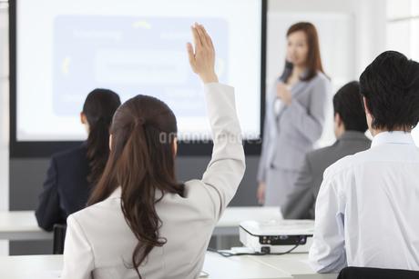 手を挙げるビジネスウーマンとビジネスマンの写真素材 [FYI01347277]