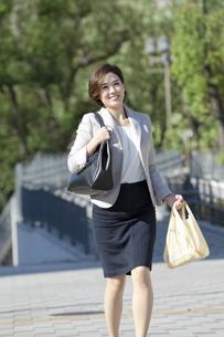 コンビニ袋を持って走るビジネスウーマンの写真素材 [FYI01347314]