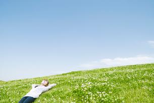草原で寝転ぶ女性の写真素材 [FYI01347922]