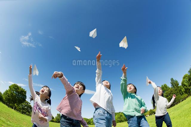 紙飛行機を飛ばす5人の子供達の写真素材 [FYI01348032]