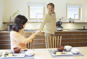 ご飯をよそった茶碗を女性に渡す男性の写真素材 [FYI01348342]