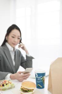 昼食とスマートフォンを持つビジネスウーマンの写真素材 [FYI01348873]