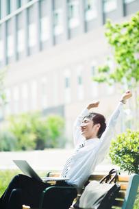 ベンチで伸びをするビジネスマンの写真素材 [FYI01350622]