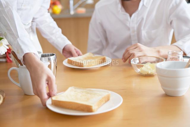 朝食を運ぶ女性の手と待つ男性の夫婦の写真素材 [FYI01350657]
