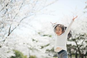 桜の前でジャンプする女の子の写真素材 [FYI01350958]