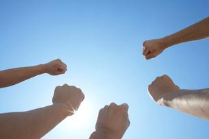 青空に力強くこぶしを突き上げる3人の男性の手の写真素材 [FYI01351594]