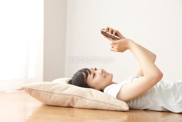 リビングの床でスマートフォンで調べ物をする女性の写真素材 [FYI01351871]