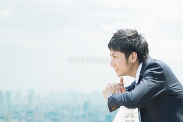 ビルの屋上で遠くを見るビジネスマンの写真素材 [FYI01352138]