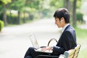 屋外でノートパソコンを操作するビジネスマンの写真素材 [FYI01352254]
