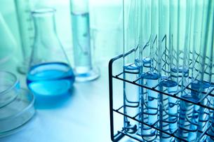 青い薬品の入ったフラスコと試験管とメスシリンダーと実験容器の写真素材 [FYI01352605]