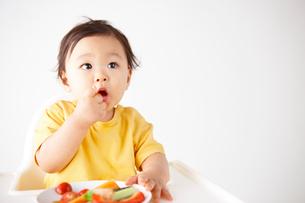 切った野菜のお皿からトマトを食べる赤ちゃんの写真素材 [FYI01352918]