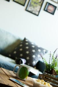 テーブルの上に置かれたスマートフォンとカップの写真素材 [FYI01354878]