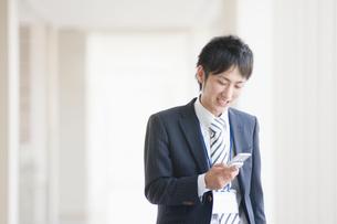 携帯電話を操作するビジネスマンの写真素材 [FYI01355155]