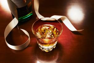 プレゼントのリボンとグラスに入ったロックのウィスキーの写真素材 [FYI01355846]