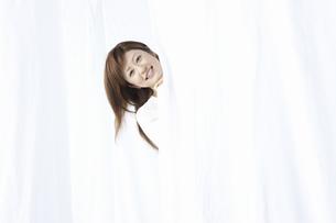 カーテン越しに微笑む女性の写真素材 [FYI01356270]