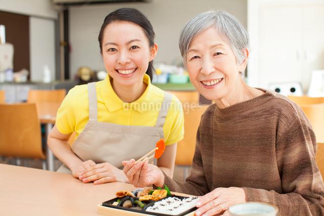 お弁当を食べるおばあちゃんと付きそう介護士の女性の写真素材 [FYI01357390]