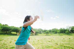 飛行機を持って走る女の子の写真素材 [FYI01358380]