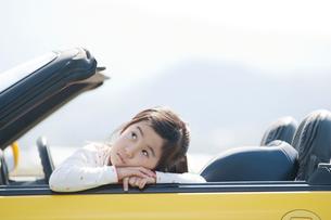 オープンカーに乗って考える女の子の写真素材 [FYI01358386]