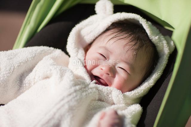 ベビーカーの上で白いベビー服を着て笑っている赤ちゃんの写真素材 [FYI01361640]
