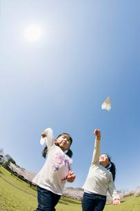 紙飛行機を飛ばす2人の子供達の写真素材 [FYI01362486]
