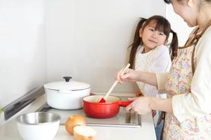 台所で赤い鍋で炒め物をする母親をみる子どもの写真素材 [FYI01362856]