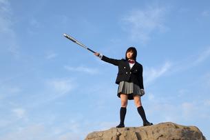 岩の上でバットを持ちポーズをとる女子高生の写真素材 [FYI01363545]