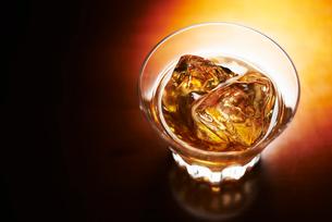 琥珀色に輝くグラスに入ったロックのウィスキーの写真素材 [FYI01363639]
