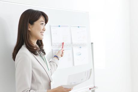 ホワイトボードの前で説明する女性の写真素材 [FYI01363865]