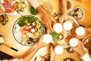 寄せ鍋を前にビールで乾杯する男女の写真素材 [FYI01364432]