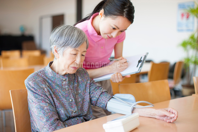 血圧を測るおばあちゃんと介護士の写真素材 [FYI01364555]