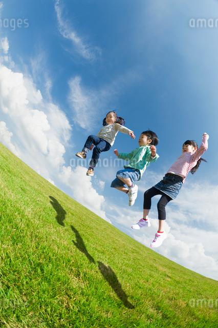 ジャンプする3人の子供達の写真素材 [FYI01364924]