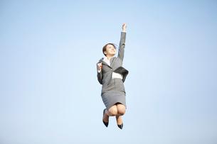 手を挙げ元気にジャンプするビジネスウーマンの写真素材 [FYI01366198]