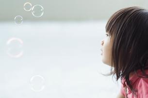 シャボン玉を見つめる女の子の写真素材 [FYI01366761]