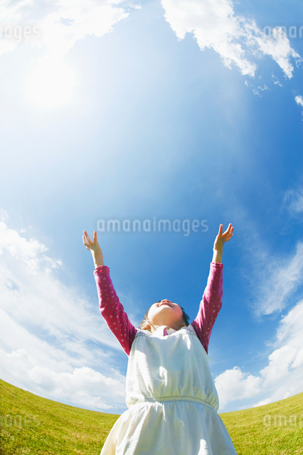 青空に向かって両手を上げる女の子の写真素材 [FYI01367076]
