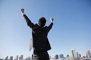 ビジネススーツを着て両手を上げて背伸びをしている男性の後姿の写真素材 [FYI01367340]
