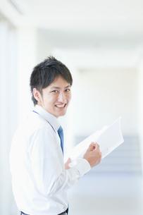 ファイルを持って微笑むビジネスマンの写真素材 [FYI01367712]