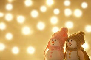 キラキラなイルミネーションの中の雪だるまのカップルの写真素材 [FYI01368016]