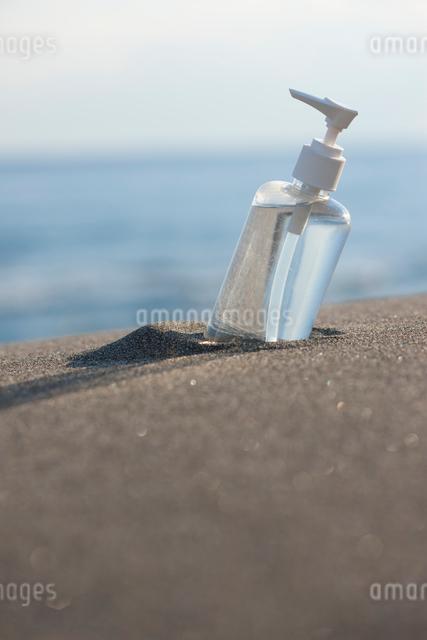 砂に埋まる化粧水の写真素材 [FYI01369659]