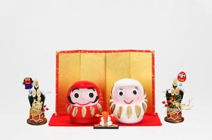 紅白のだるまのカップルと鏡餅と金屏風の写真素材 [FYI01370355]