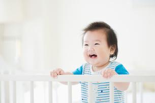 ベビーベッドで笑う赤ちゃんの写真素材 [FYI01370790]